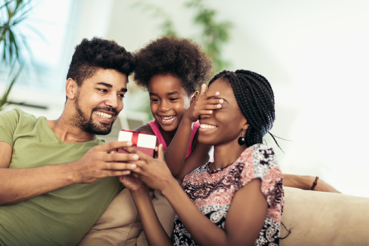 black mother, father, and daughter opening present on couch