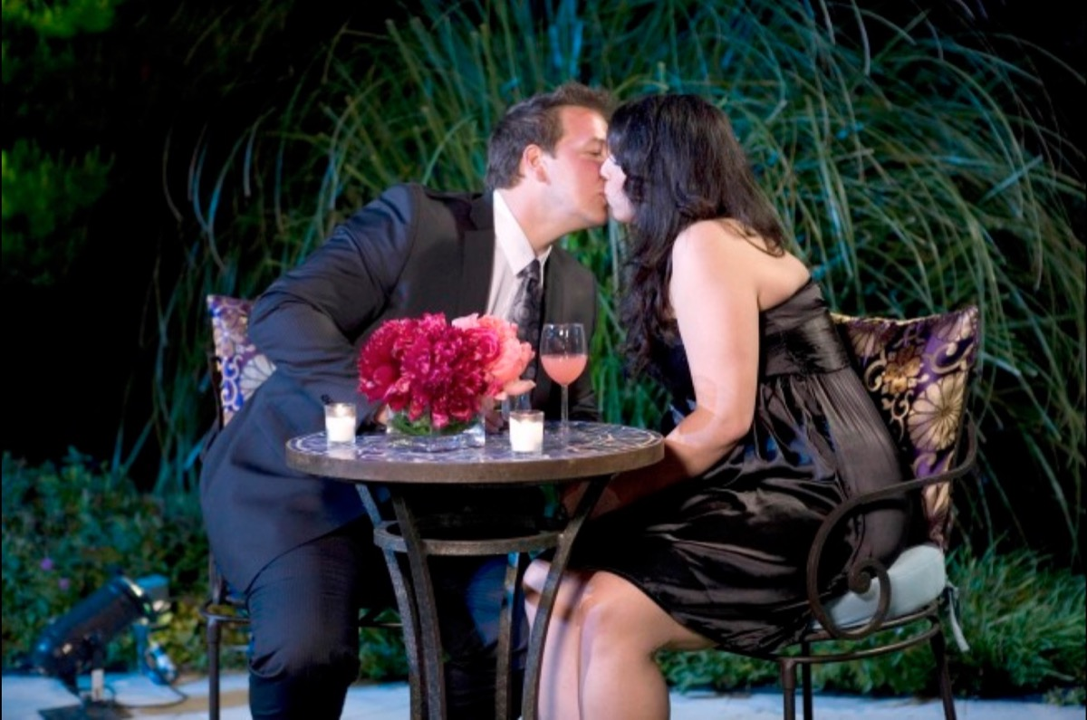 white man in suit kissing woman in strapless dress