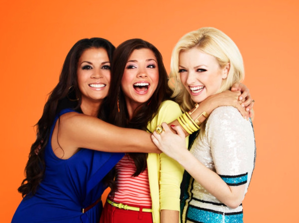 middle aged woman with dark hair hugging brown-haired girl and blond girl