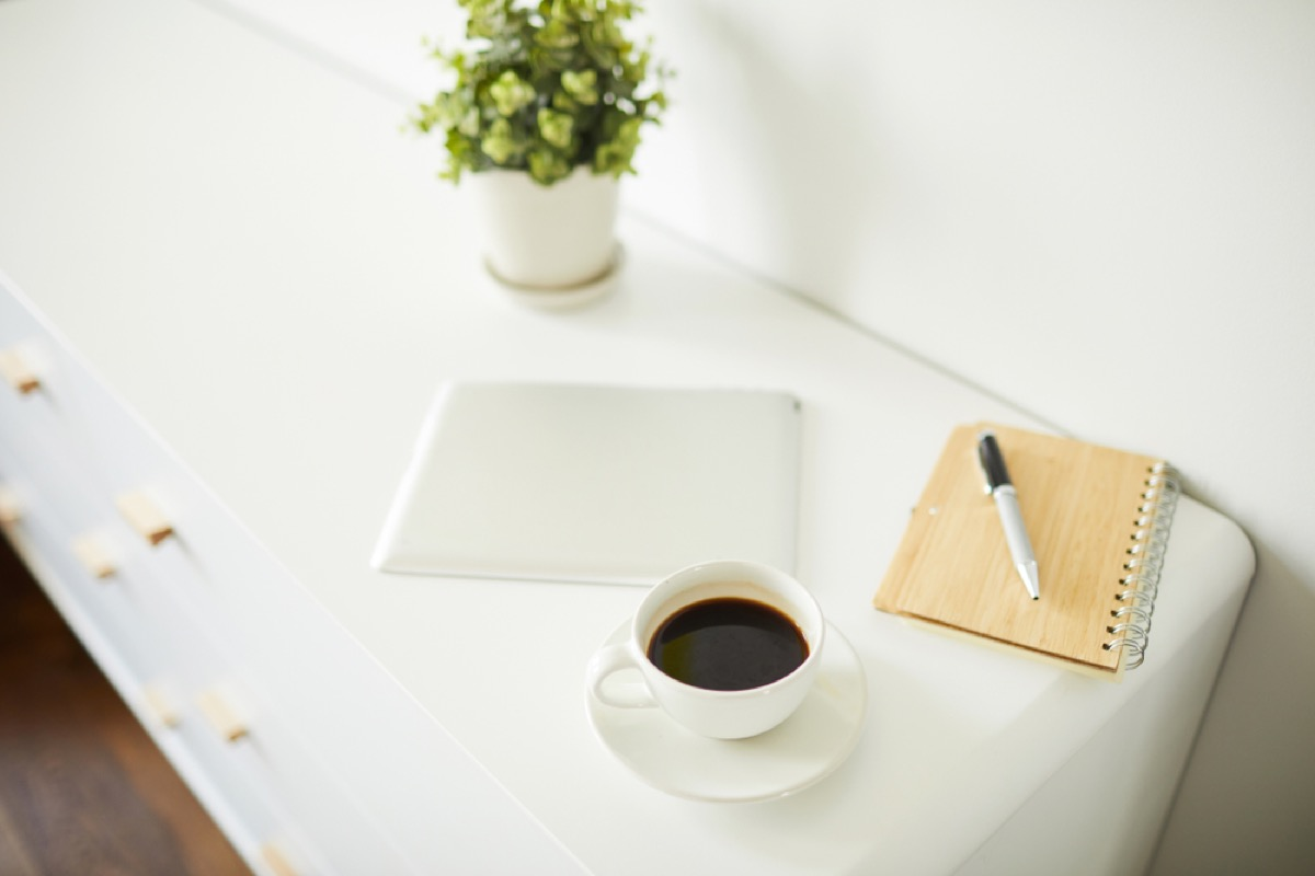 white nightstand with notebook, coffee, tablet, and plant on it