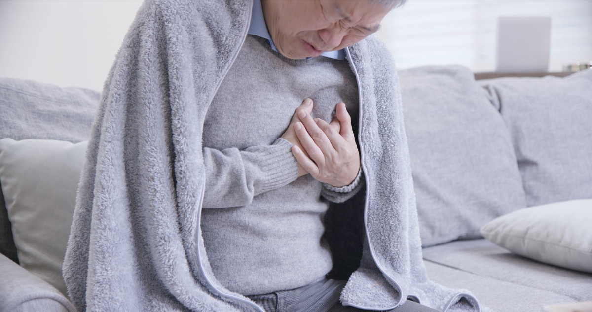 Man sitting on the couch with a blanket holding his chest in pain
