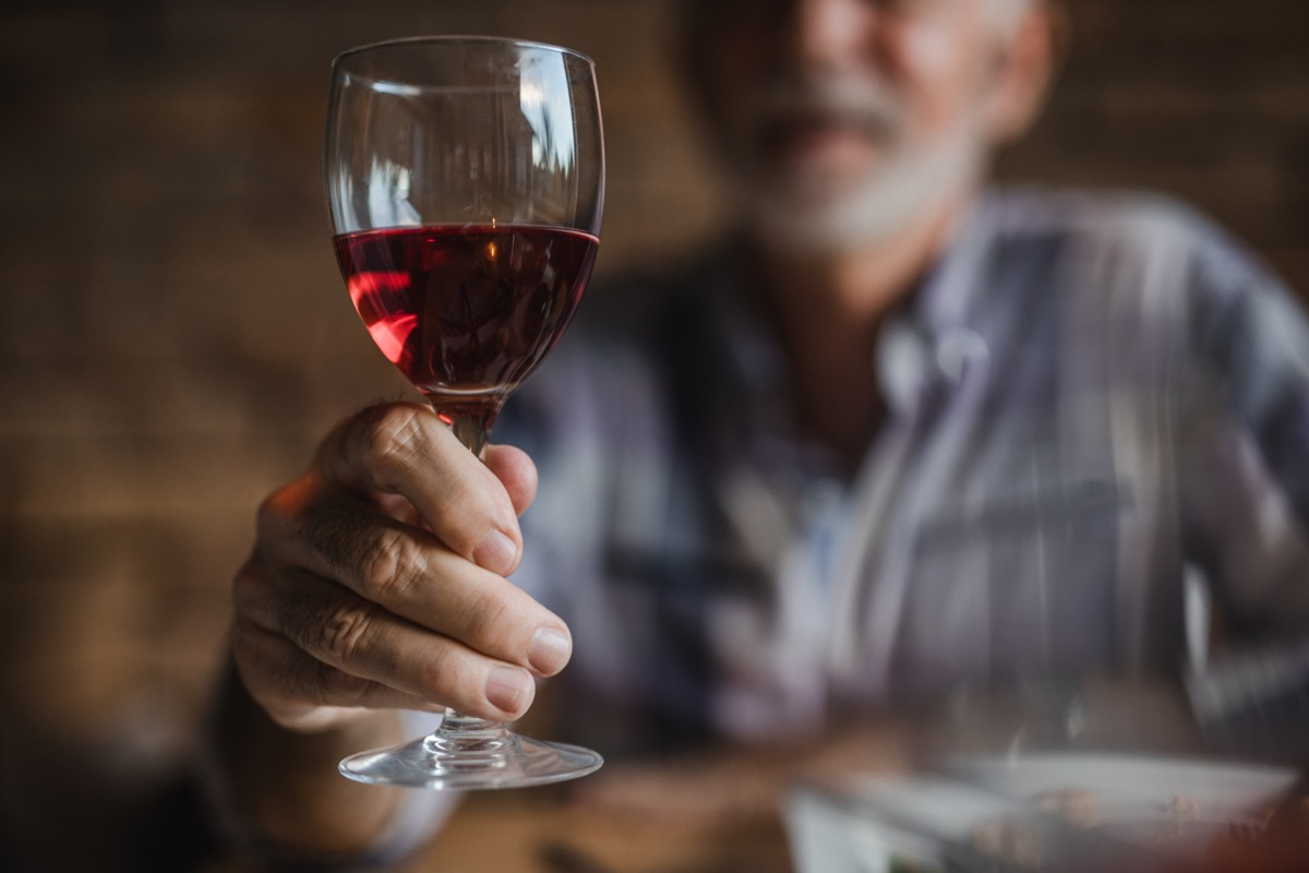 older man holding a wine glass of red wine