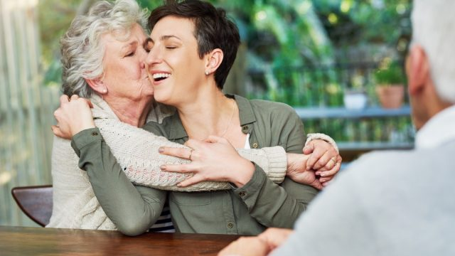 older woman kissing adult duaghter