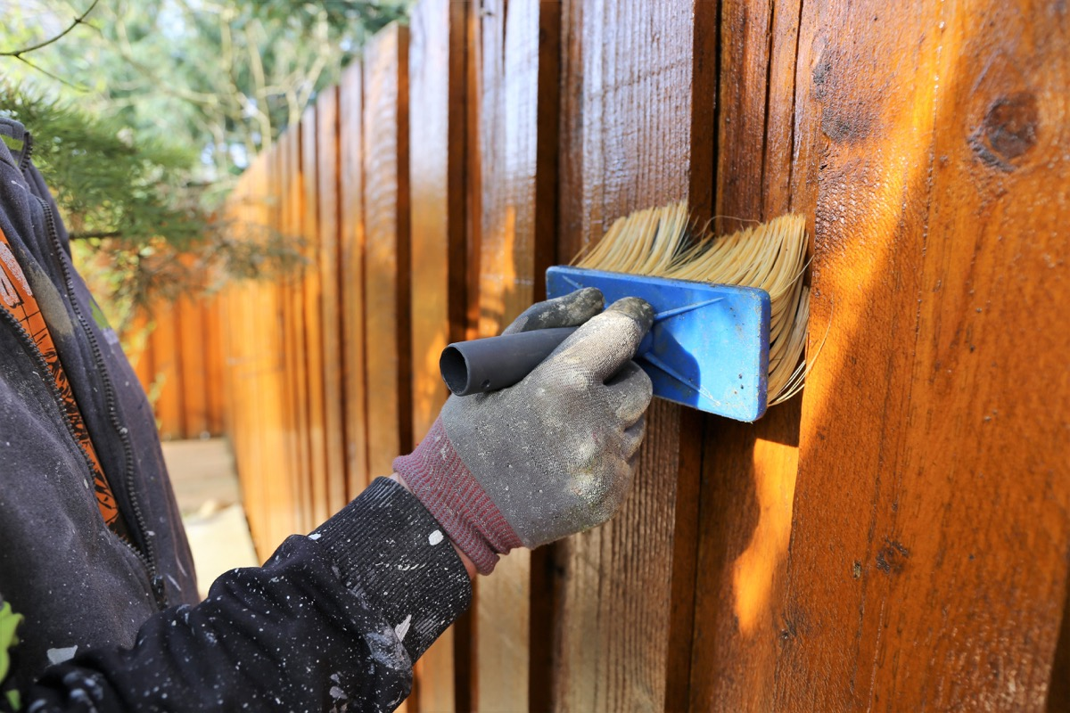someone painting an outisde fence