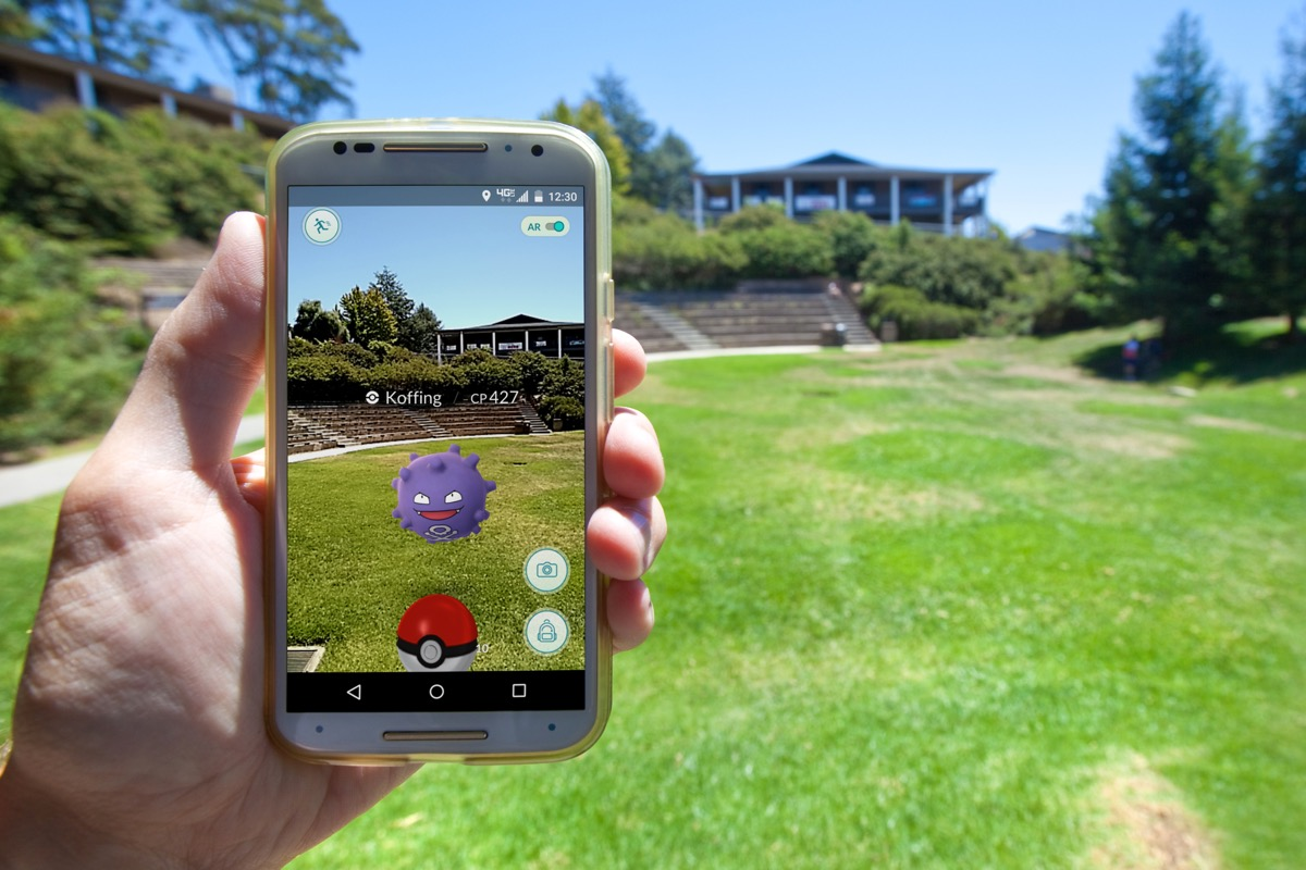 person holding phone with pokemon go game open