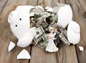 A broken piggy bank with crumpled bills and a wedding cake couple.