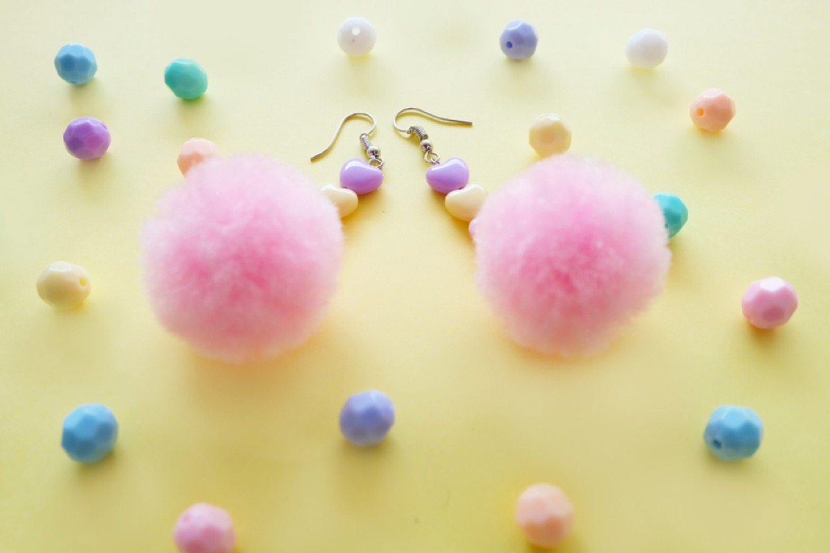 pink pom pom earrings on yellow background with pastel colored heart beads