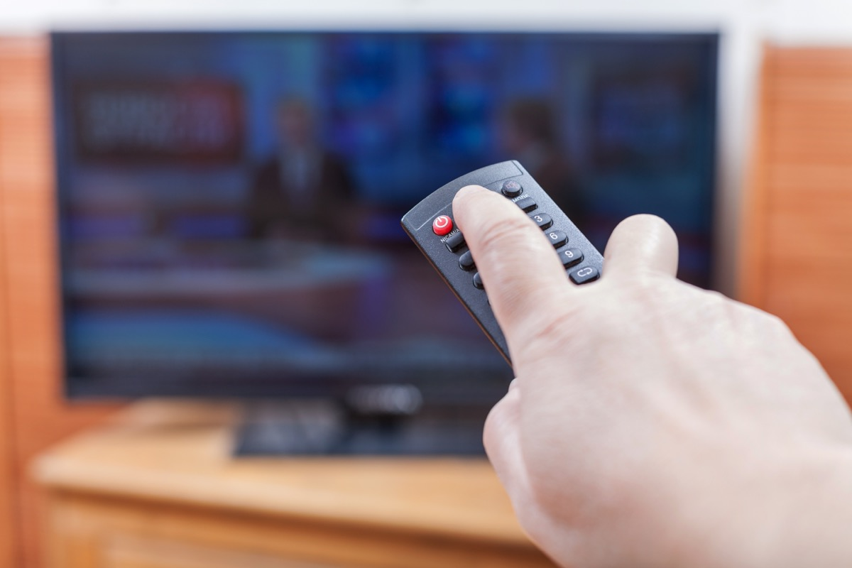 Person using a television remote to turn off their TV
