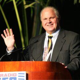 rush limbaugh standing at podium and waving