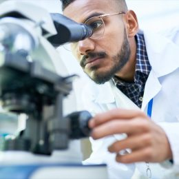 Scientist in the lab using a microscope