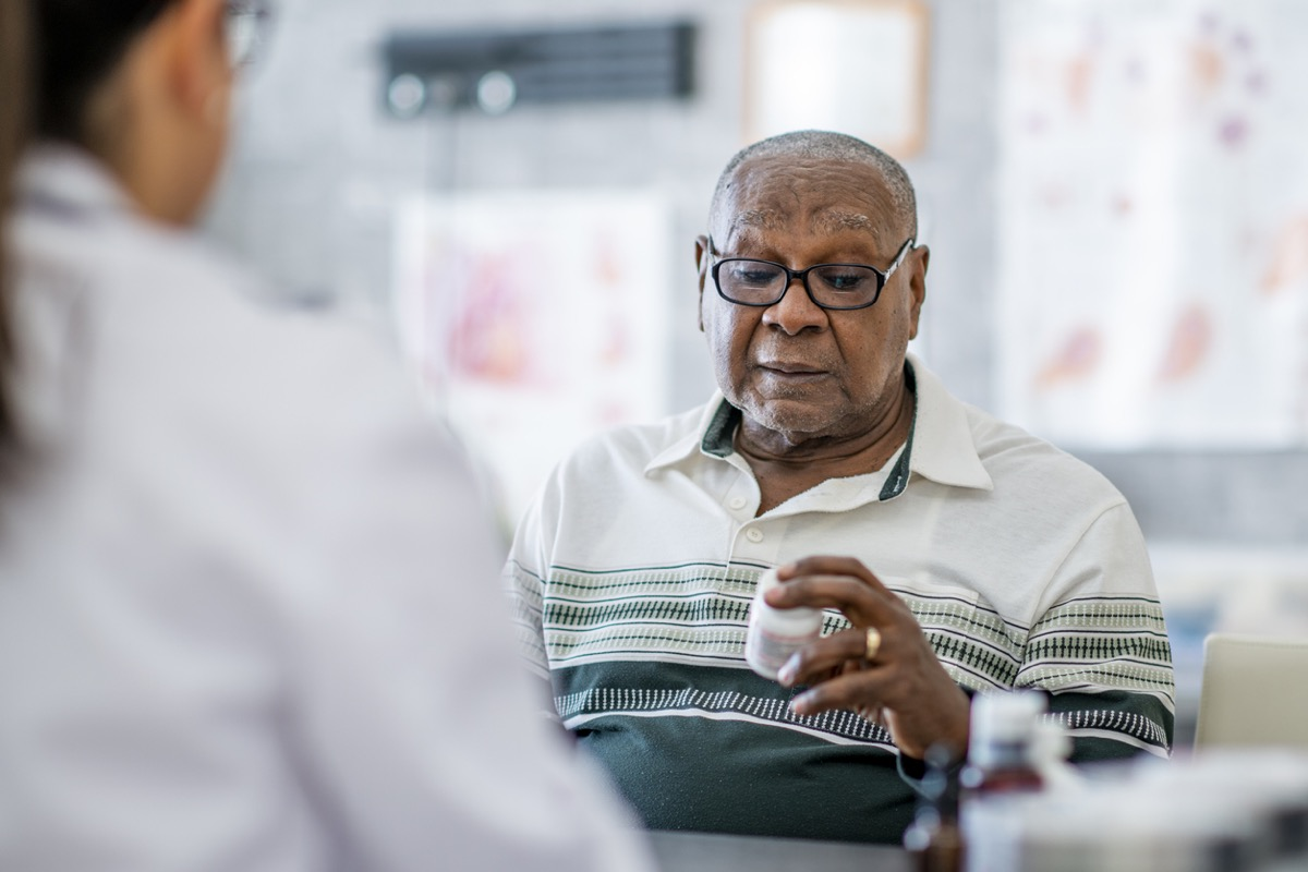 An elderly black man looks at a pill bottle in his hand while sitting across the table from a doctor in the doctor's office. He appears to be making a decision about it.