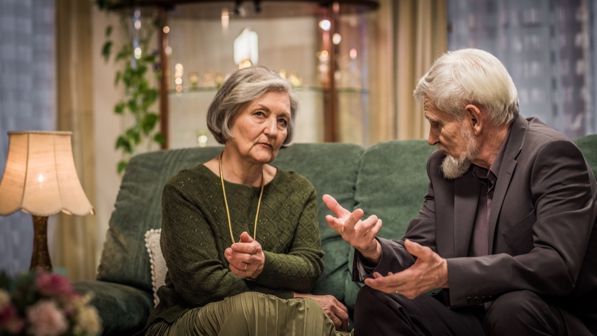 Elderly couple sitting on the living room sofa and having a serious conversation.
