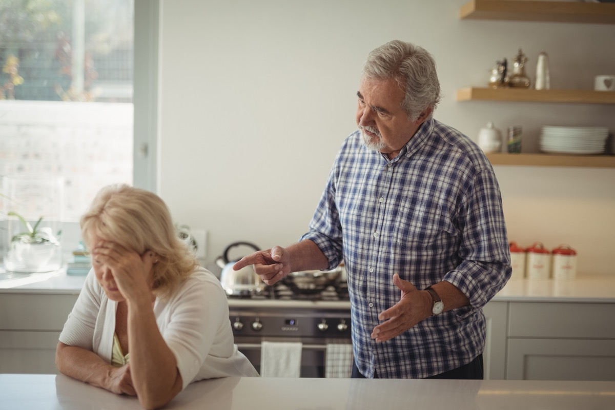 Senior couple arguing in kitchen at home, woman leans on island with head in hands
