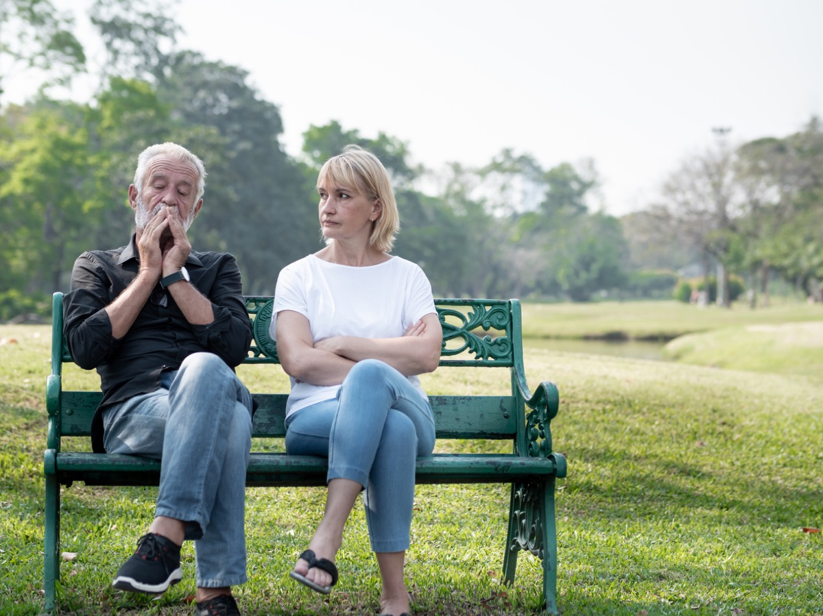 Senior couple having problems in the park, both have legs crossed
