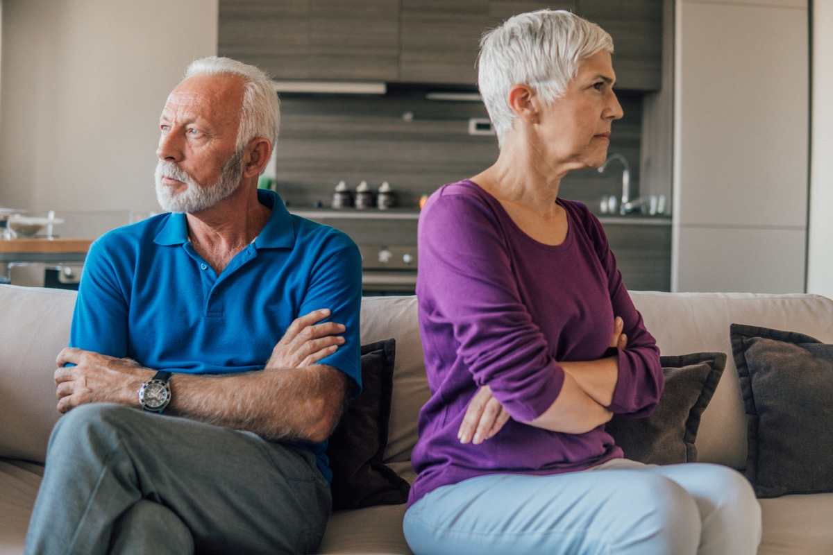 Senior married couple having an argument as they look away from each other with arms folded on couch