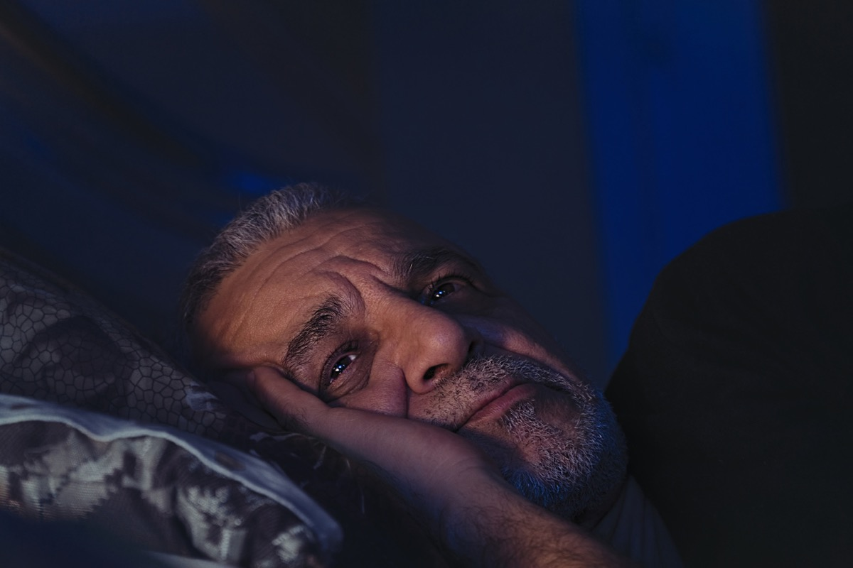 Senior man up in the middle of the night with eyes open and furrowed brow