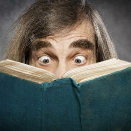 senior man looks shocked reading book