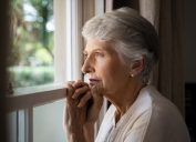 senior woman looks out the window