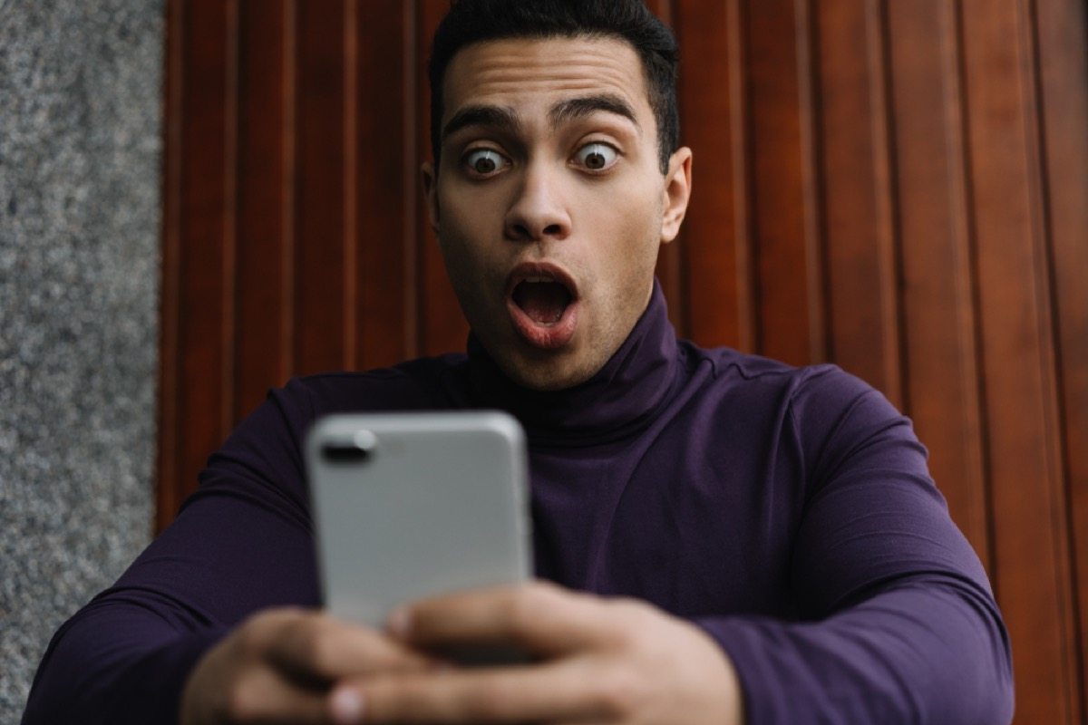 man of color looks shocked at phone