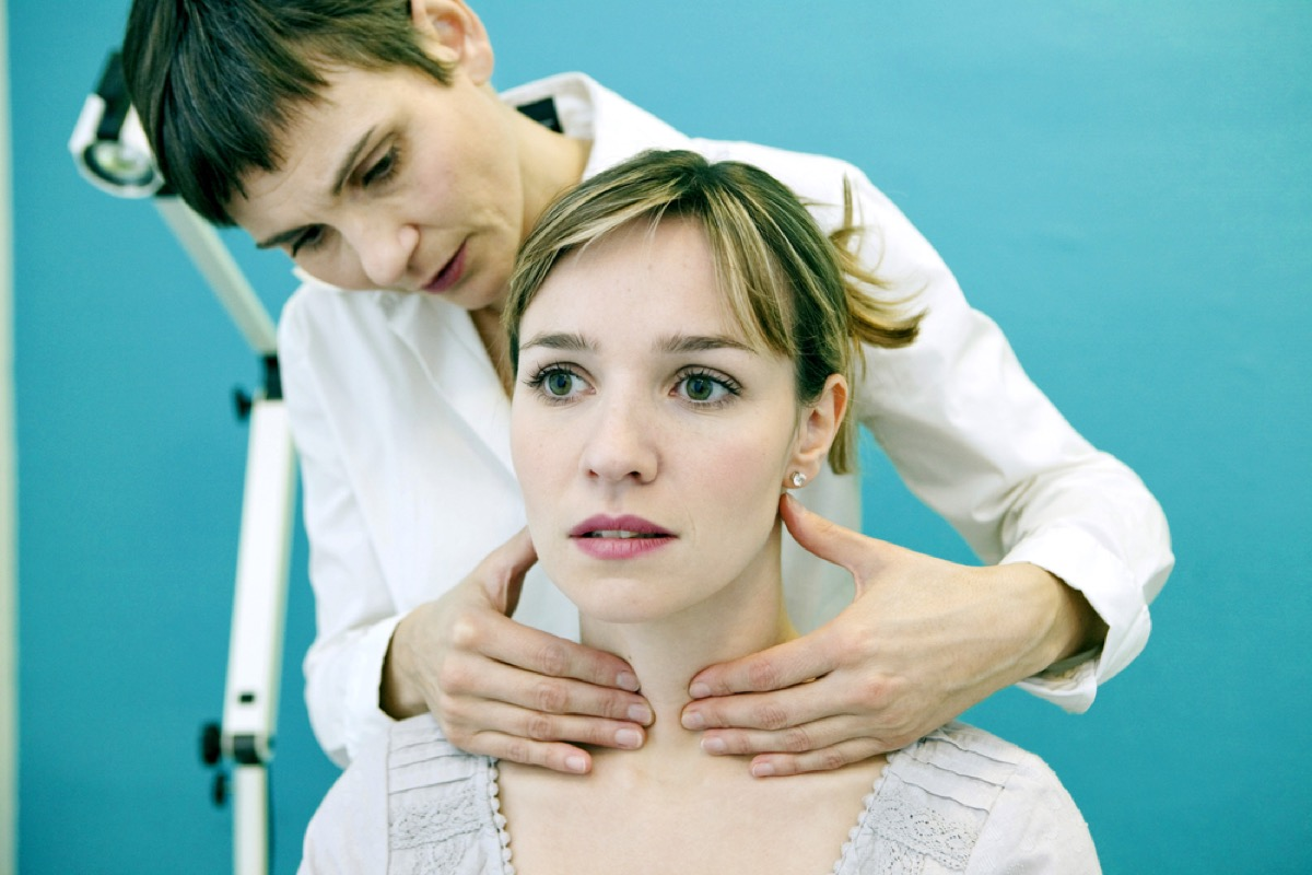 young white woman having thyroid checked by female doctor