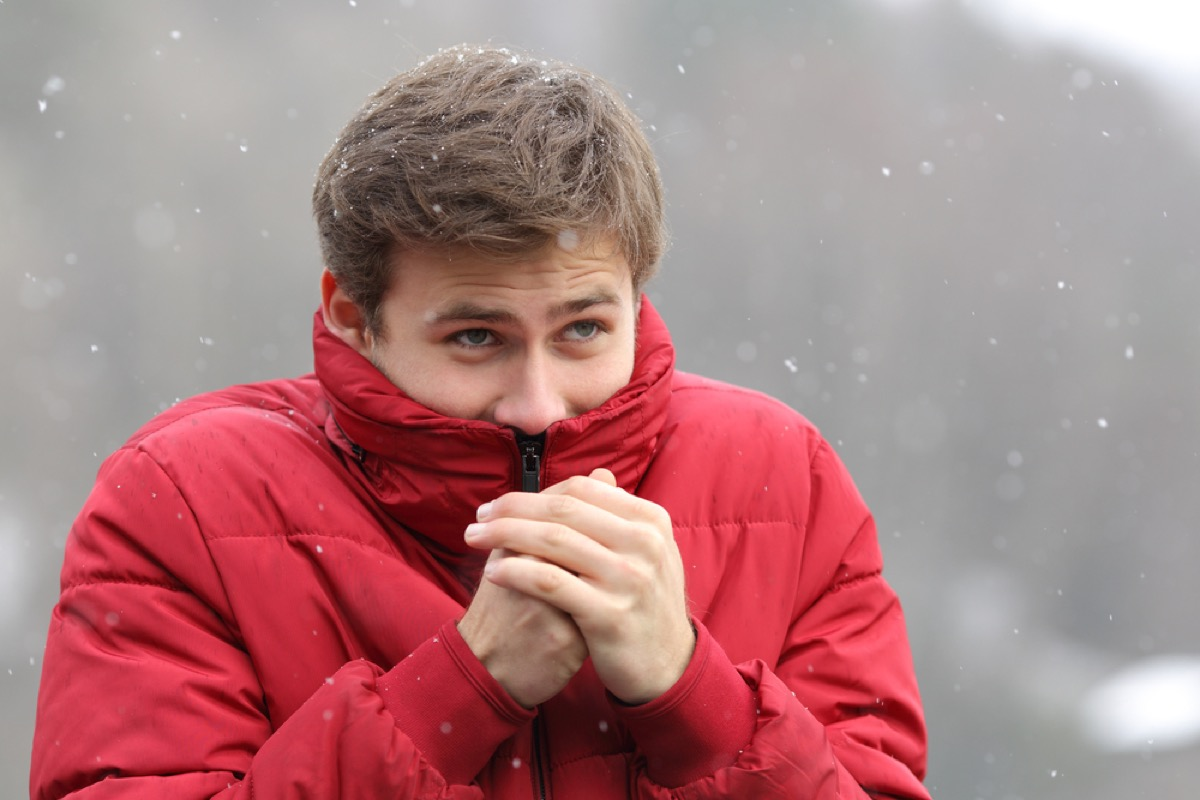 white man in snow with jacket pulled up over his face