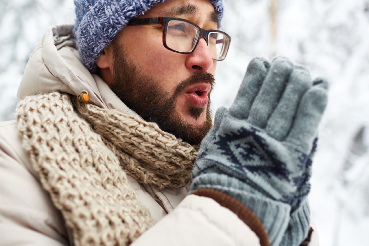 asian man outside in snow in winter clothing