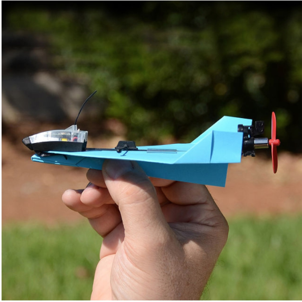white hand holding blue smartphone controlled paper airplane