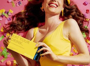 white woman in yellow dress holding yellow box against pink background covered in candy