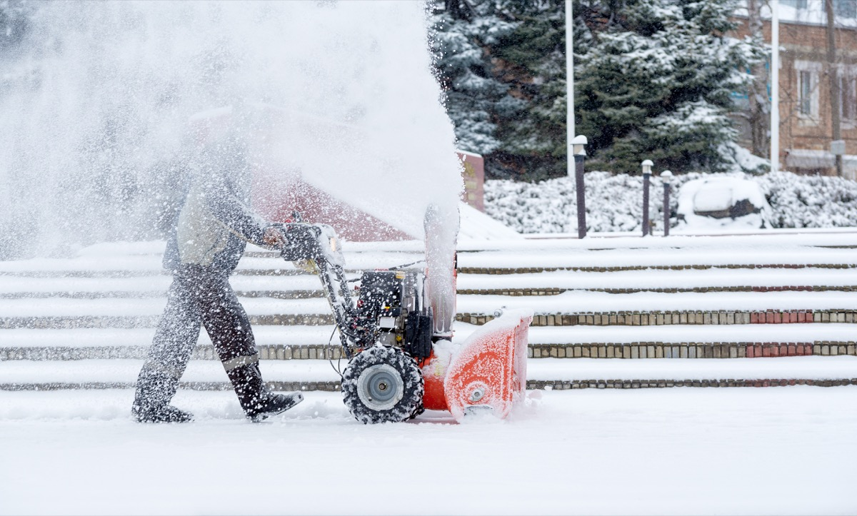 man using a snowblower in the yard