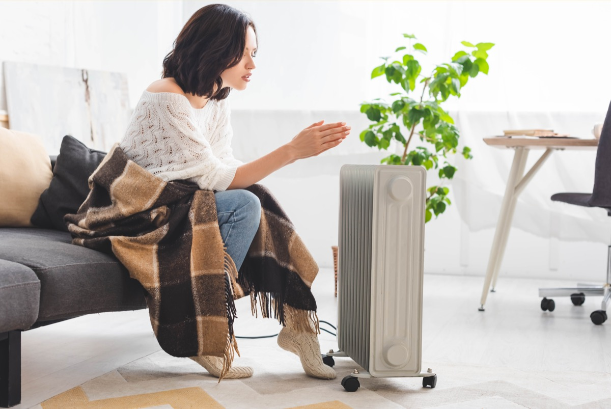 woman warming up next to a space heater