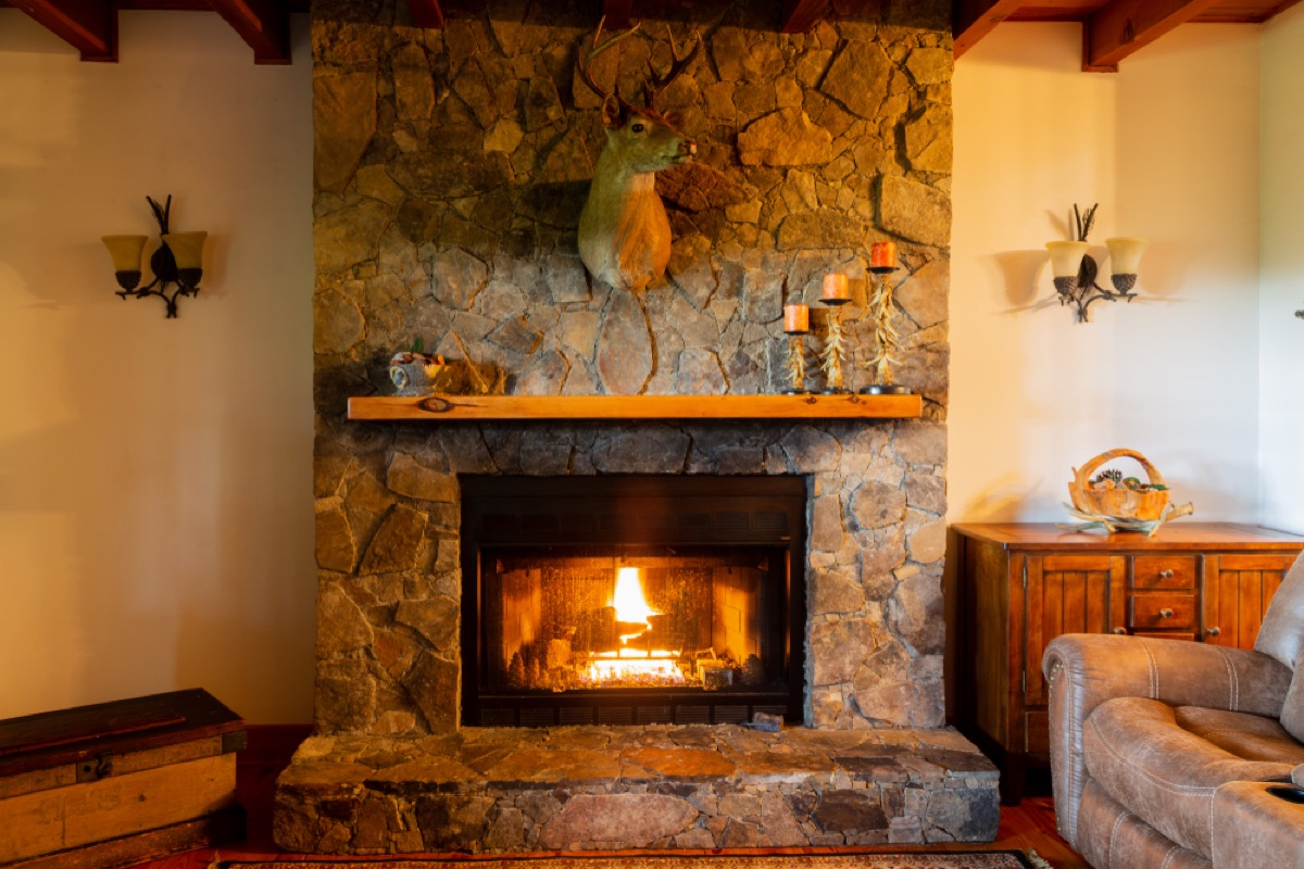 stone fireplace and wood mantle with deer head taxidermy