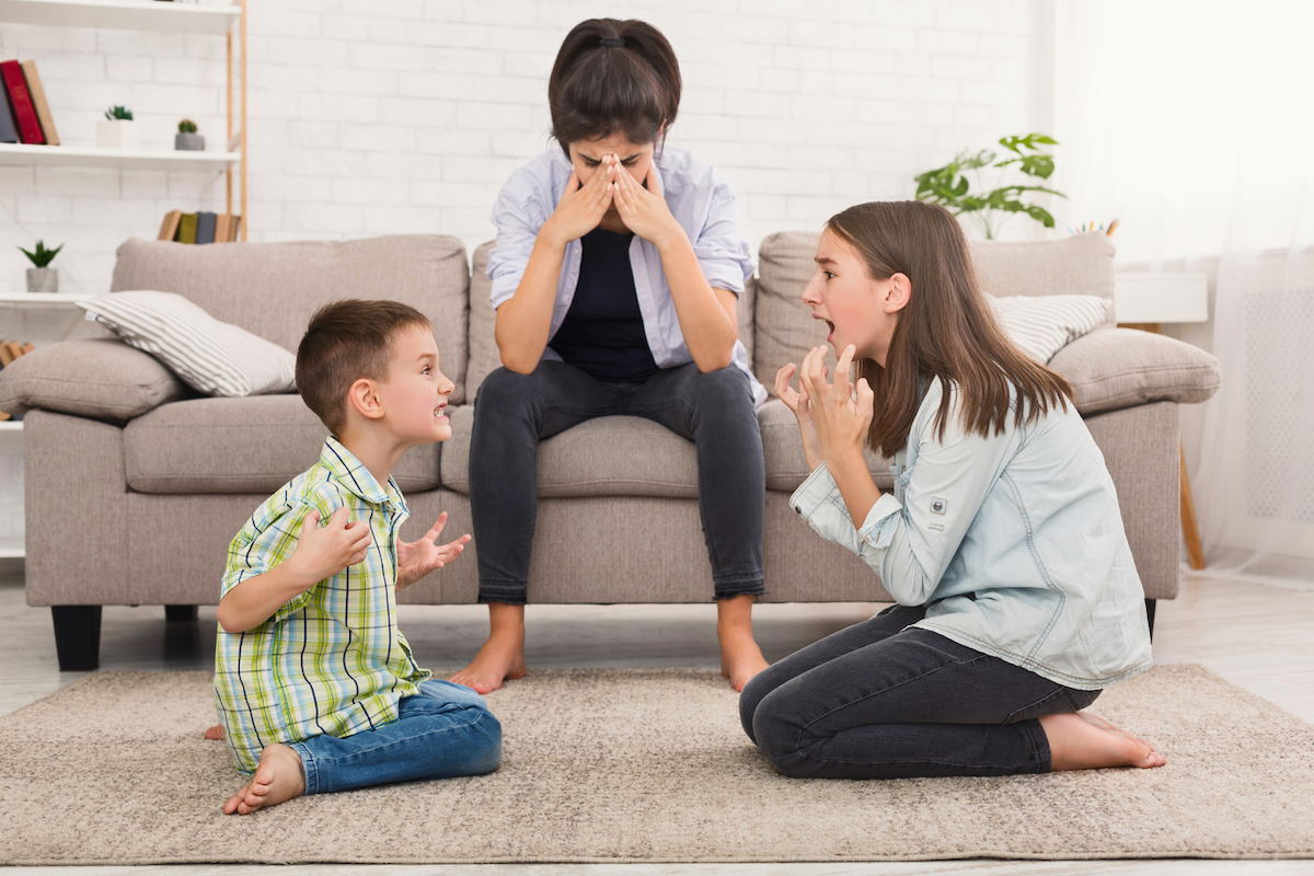 Mom is stressed by screaming children fighting with each other