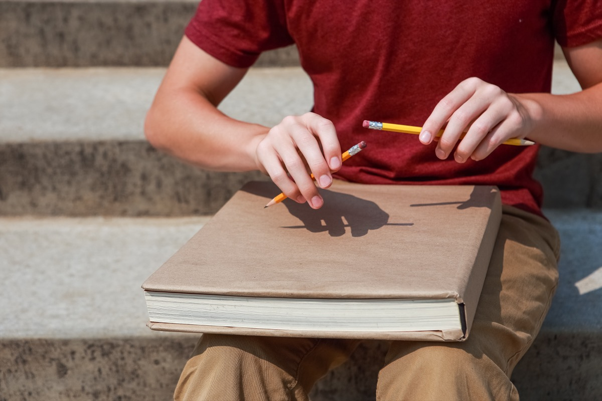 Boy feeling antsy and tapping his pencils on his notebook