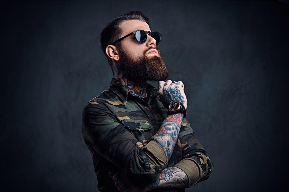 tattooed bearded hipster posing