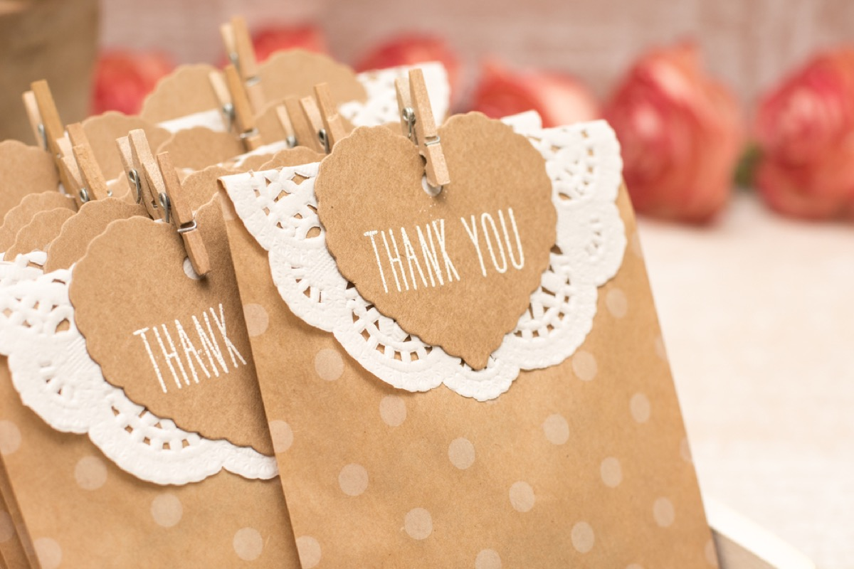 brown paper gift bags with white doily and thank you note clothes-pinned to it