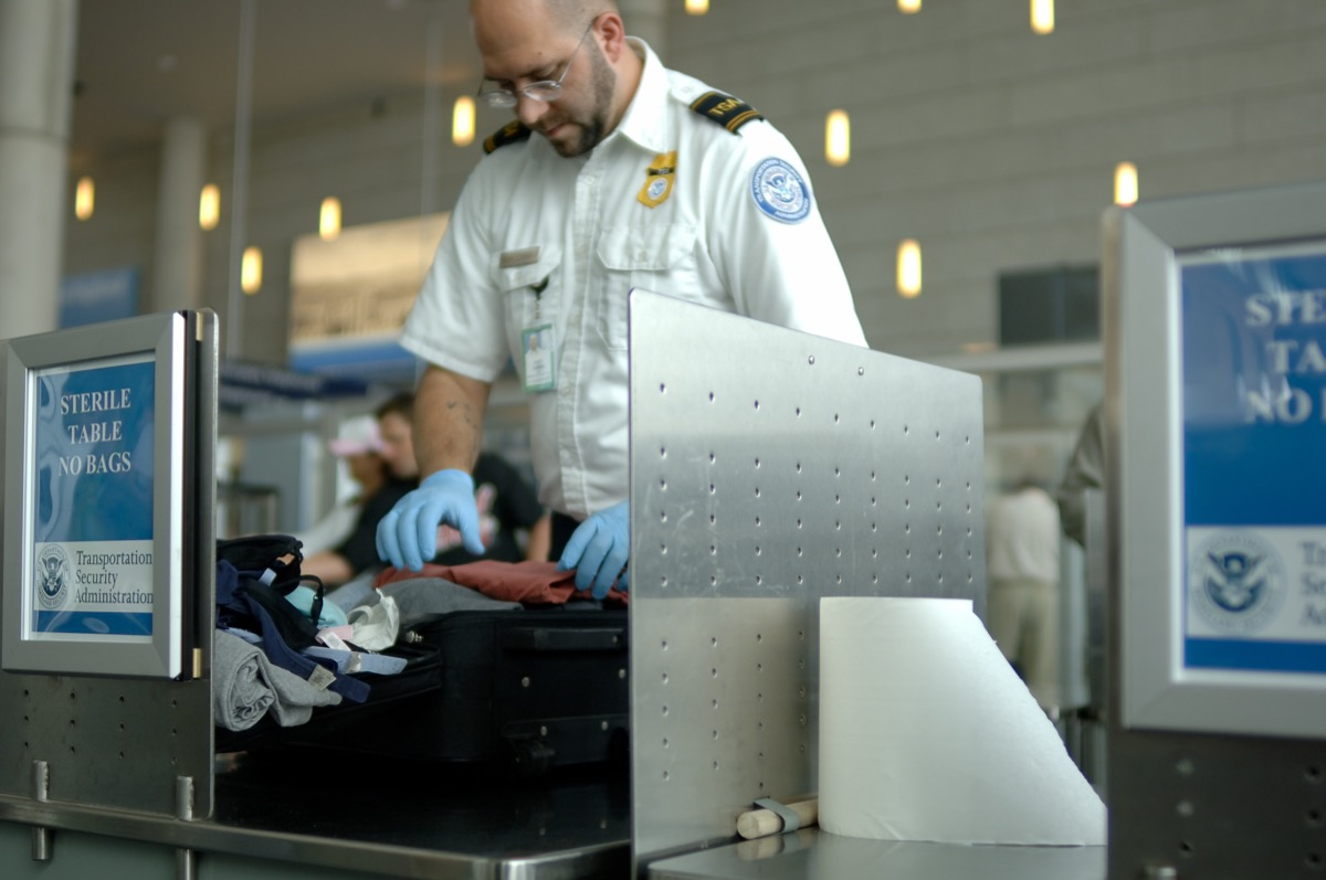 TSA agent searching through someone's luggage at the airport
