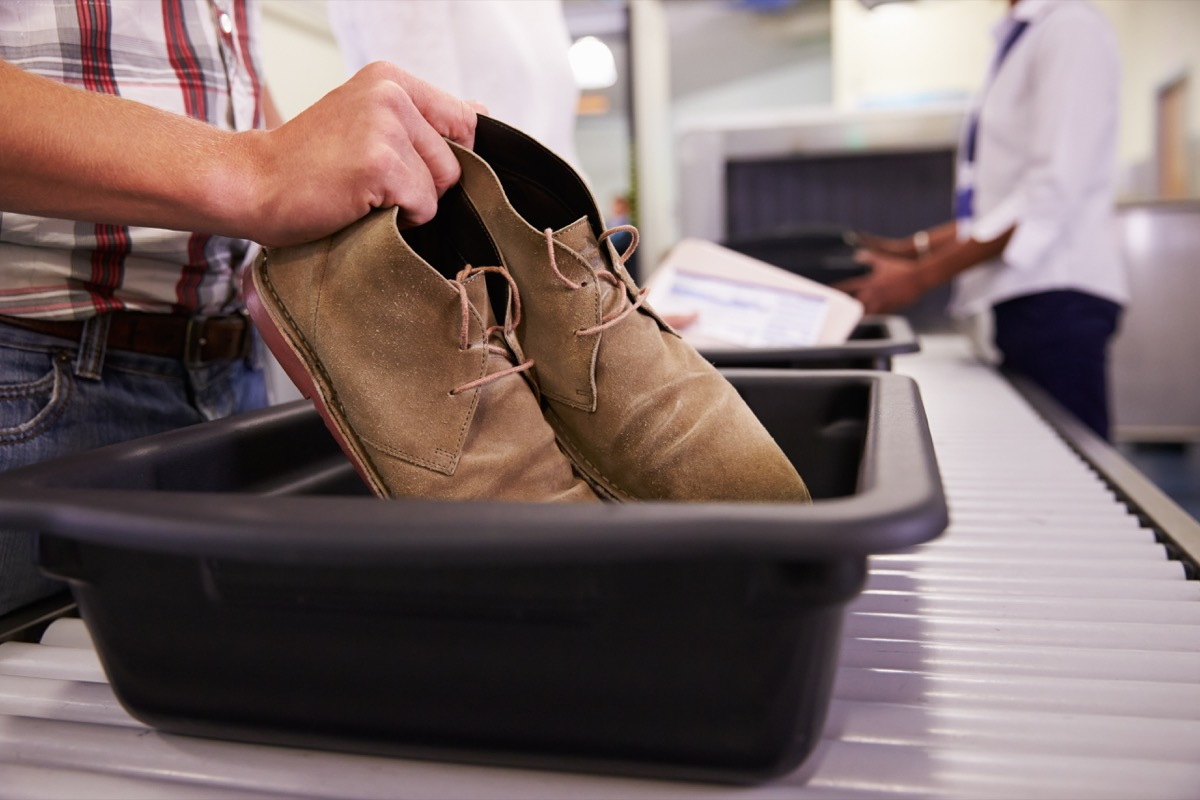 Man putting his shoes in a bin in the airport security line