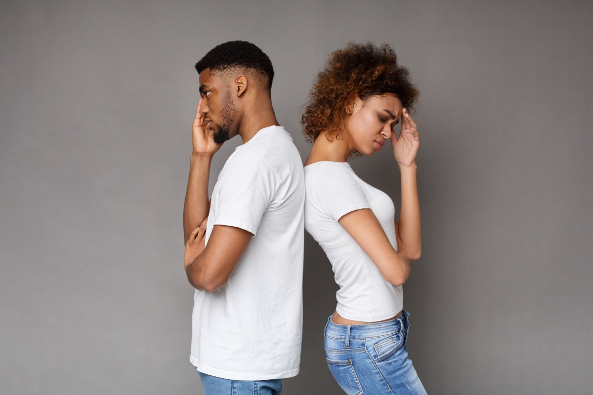 unhappy man and woman standing back to back
