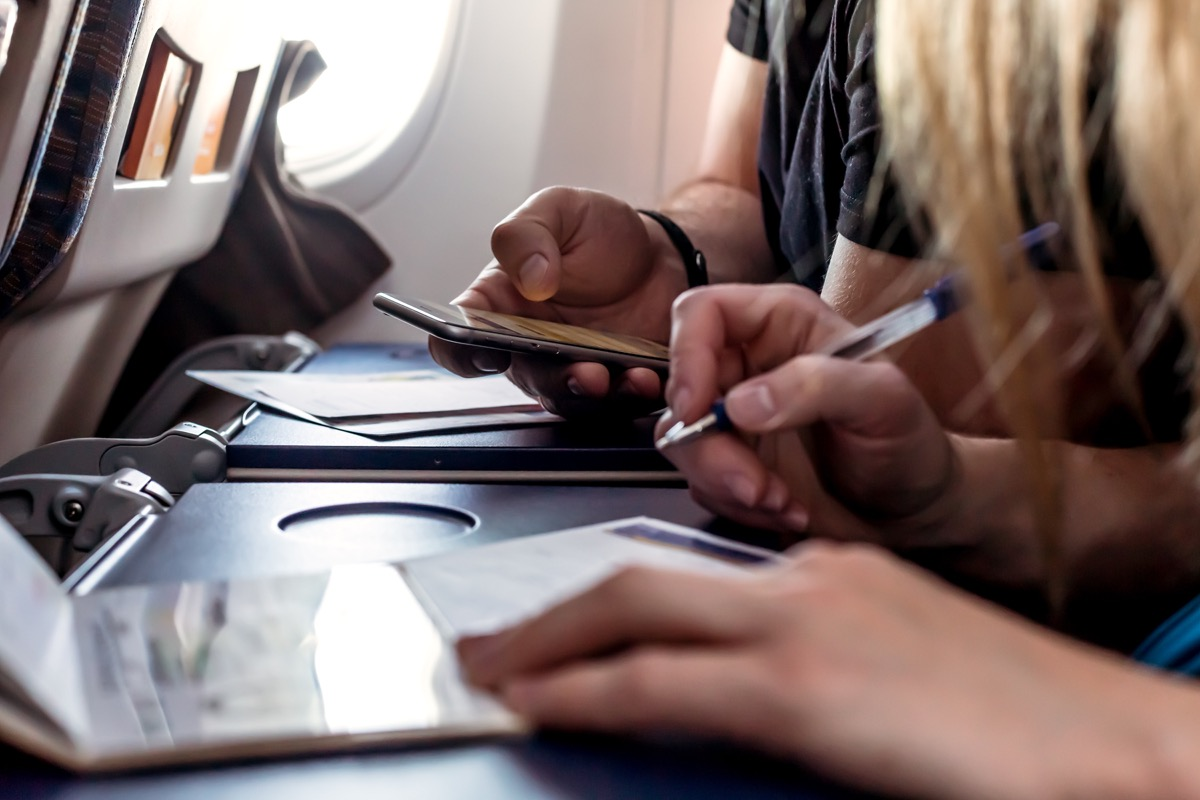 People filling out forms on an airplane tray table
