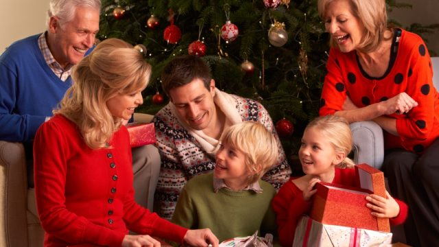 white grandparents, mother, father, and young daughter opening gifts