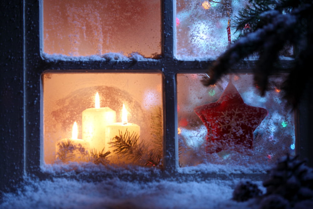 winter window has snow on sill with candles inside