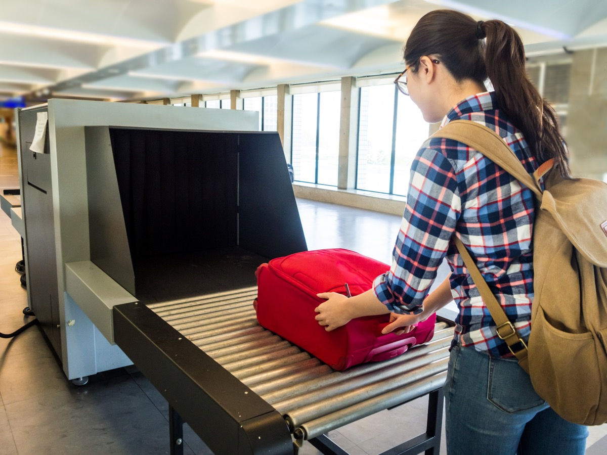 Woman putting her bag through airport security check