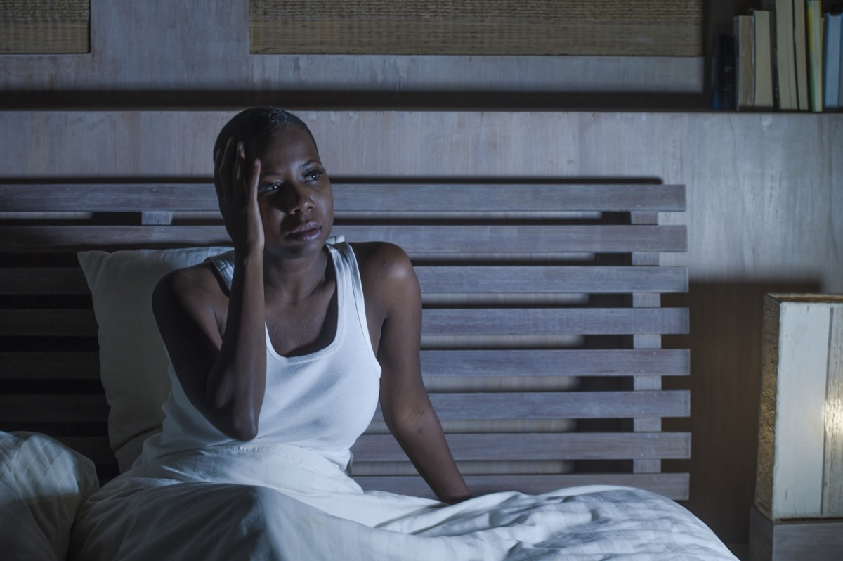 Black woman sitting awake in bed at night