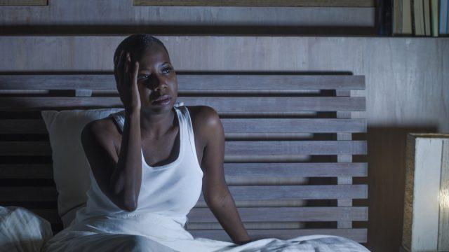 Woman sitting awake in bed at night