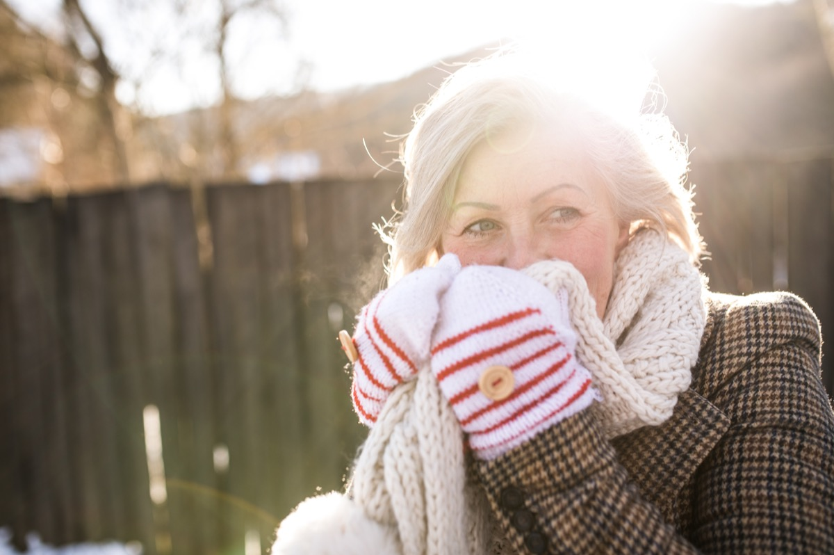 Woman outside in the cold using a scarf to warm her face in the winter
