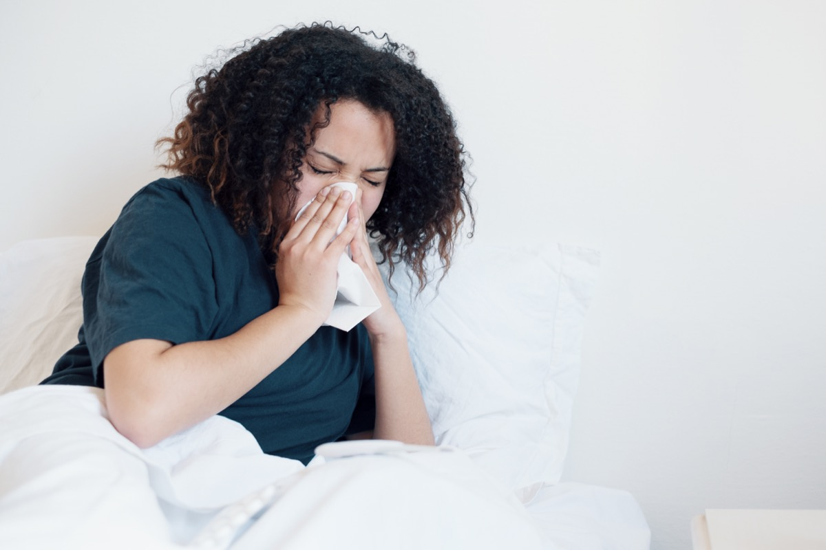 Woman sick and coughing in bed