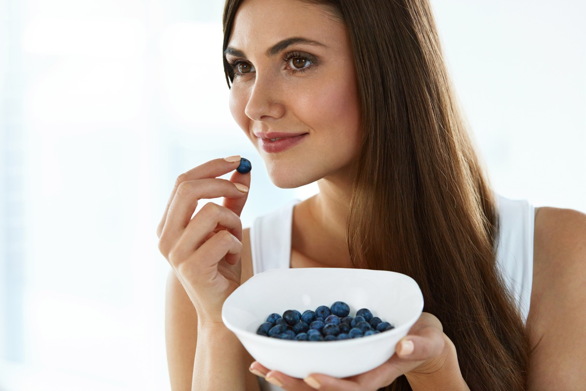 Woman snacking on some blueberries
