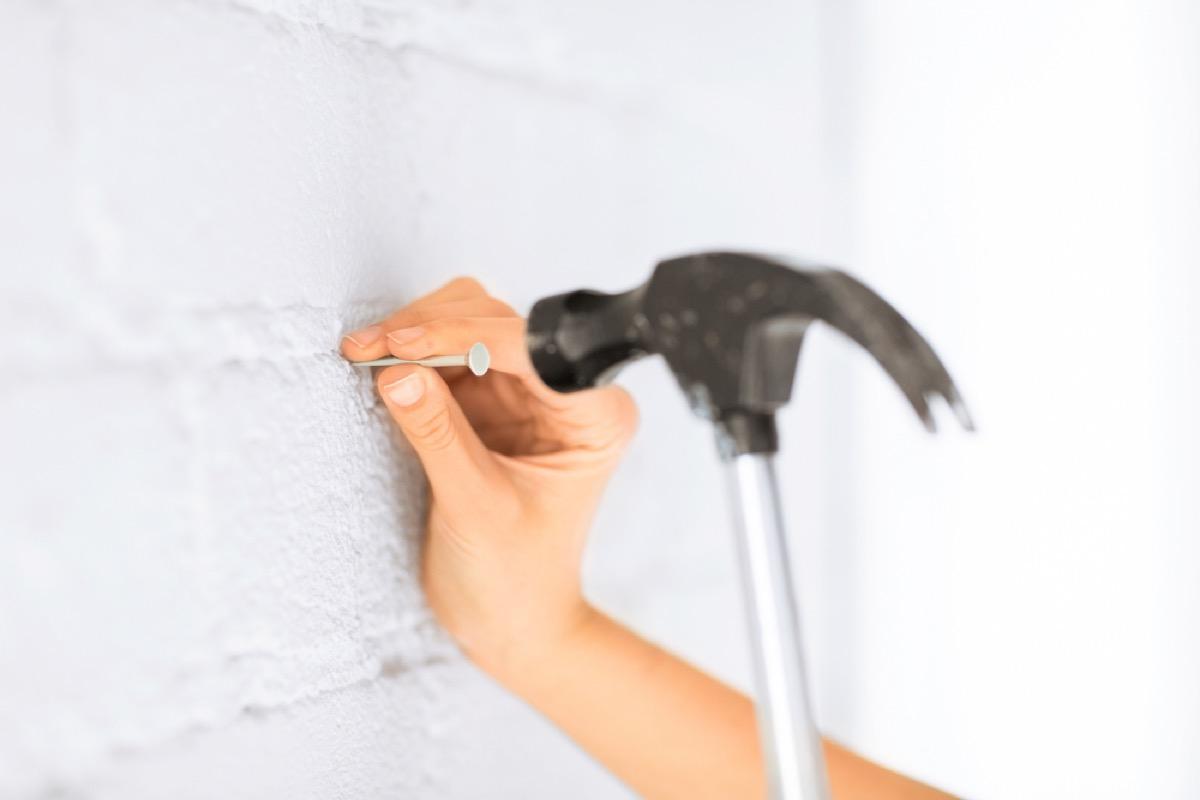woman hammering nail into white brick wall