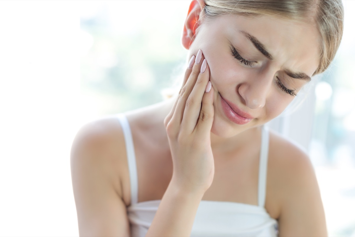 woman rubbing face in pain
