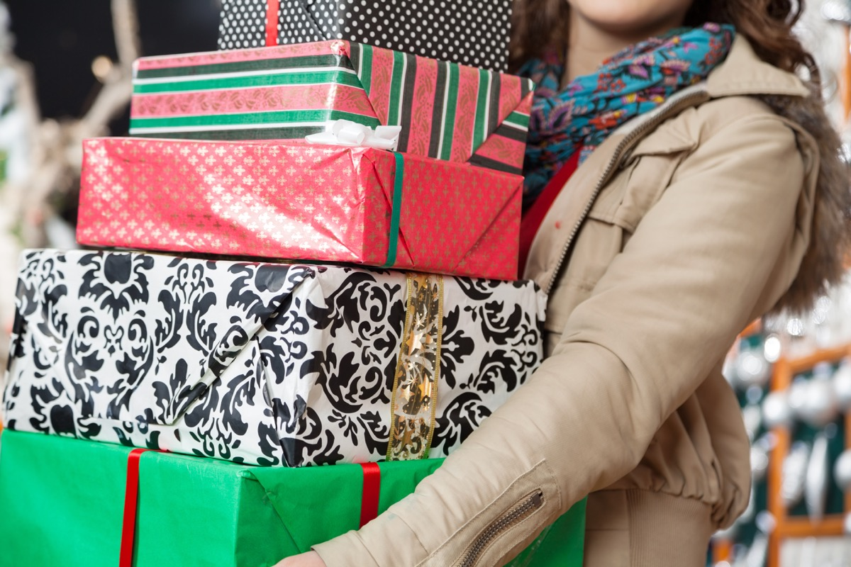 Woman holding a pile of wrapped presents